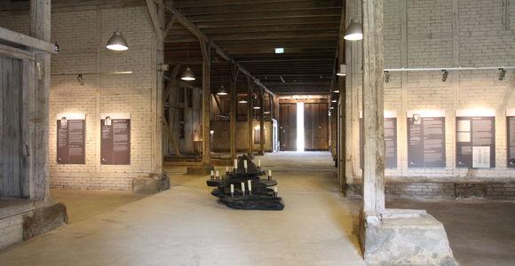 Blick in die Ausstellung zum Außenkommando Laura in der ehemaligen Häftlingsunterkunft. Im Vordergrund ein Altar mit brennenden Kerzen.
