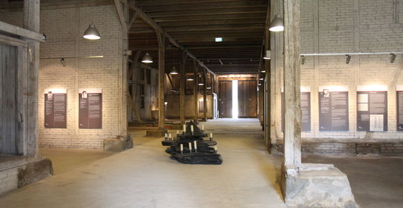 The image shows the inside of the barn with parts of the exhibition and the slate altar.