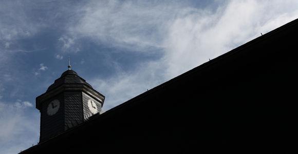 Blick zur Turmuhr auf der ehemaligen Häftlingsunterkunft