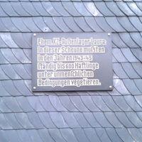 Auf der Tafel steht folgender Text: Ehemaliges KZ-Außenlager Laura: In dieser Scheune mussten in den Jahren 1943 bis 1945 ständig bis zu 600 Häftlinge unter unmenschlichen Bedingungen vegetieren.