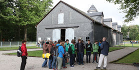A group of students in front of the great barn - the former main accommodation of inmates