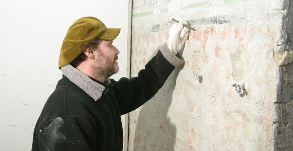 Bei der Rastaurierung einer Wandzeichnung in der ehemaligen Häftlingsunterkunft